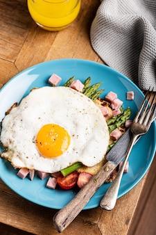 Overhead schot van ontbijt of lunch met gebakken ei, brood, toast, groene asperges, tomaten en spek op blauw bord