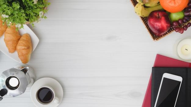 Overhead schot van ontbijttafel met kopie ruimte, telefoon, laptop, fruitmand, croissant, koffiekopje en mokapot