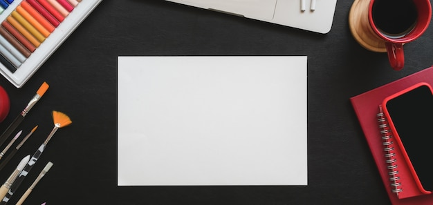 Overhead schot van trendy kunstenaar studio met schets papier en tekengereedschappen op zwarte tafel