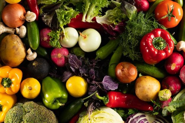 Overhead schot van verschillende verse groenten, samengesteld op een zwarte achtergrond