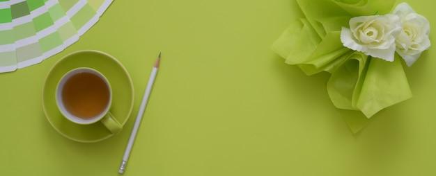 Overhead schot van werkruimte met kopie ruimte, kopje thee, gekleurd staal en decoratie op groene tafel
