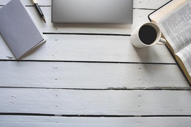 Overhead schot van wit houten oppervlak met laptop, bijbel, koffie en een notitieblok met een pen erop
