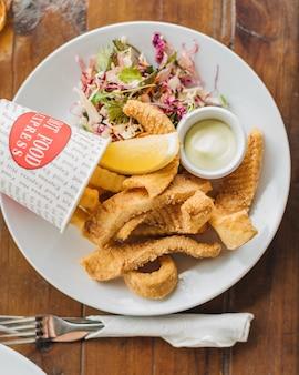 Overhead selectieve close-up shot van een groente salade, fish chips en mayonaise op een witte plaat