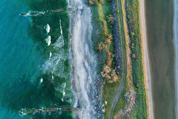 Overhead shot van een smalle kust in het midden van de zee met pad en groen erop