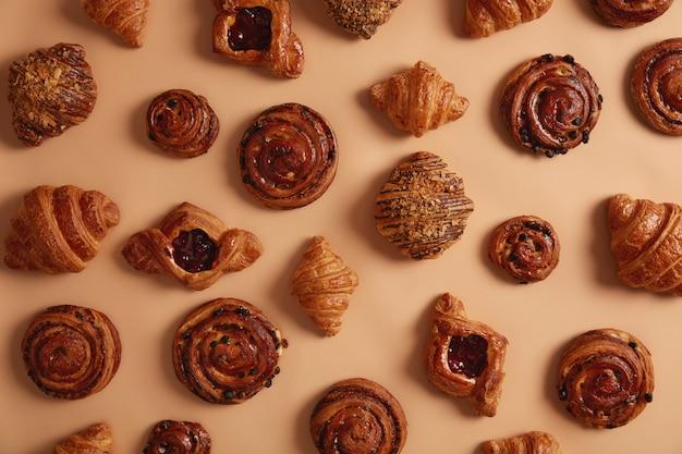 Overhead shot van smakelijke, heerlijke zoete zoetwaren die veel suiker bevatten en die zwaarlijvigheid en chronische ziekten kunnen veroorzaken. diverse croissants, broodjes en swirls om uit te kiezen in bakkerswinkel