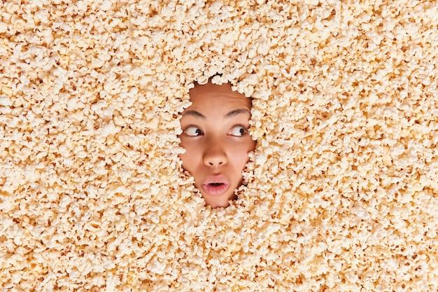 Overhead shot van verraste jonge vrouw begraven in popcornn eet smakelijke snack terwijl ze naar de bioscoop gaat, weggefocust met geschokte uitdrukking. extra calorieën. gewichtsverlies dieet concept Gratis Foto