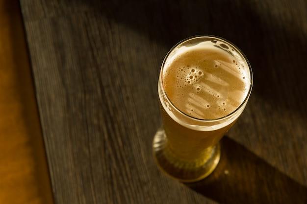 Overhead van een glas bier op tafel in zonlicht