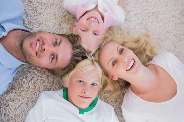 Overhead van familie op het tapijt liggen