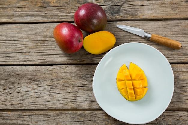 Overhead van gehalveerde en gehakte mango's met mes op houten tafel