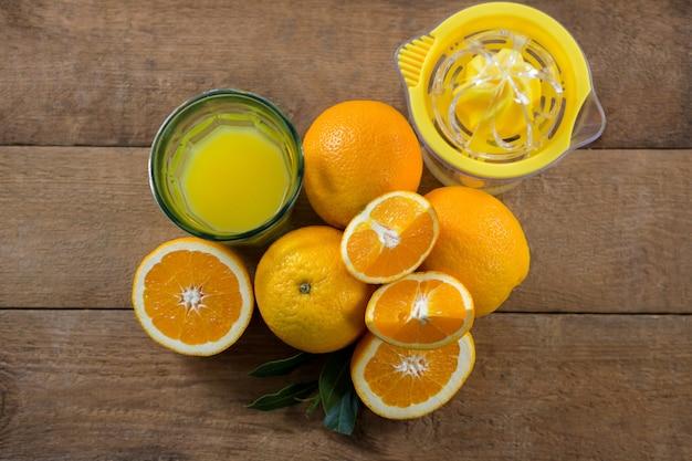 Overhead van sinaasappelen met glazen sap en fruitpers op houten tafel