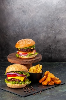 Overheerlijke heerlijke sandwiches frietjes kipnuggets op zwarte bord frietjes peper op donkergrijs wazig oppervlak