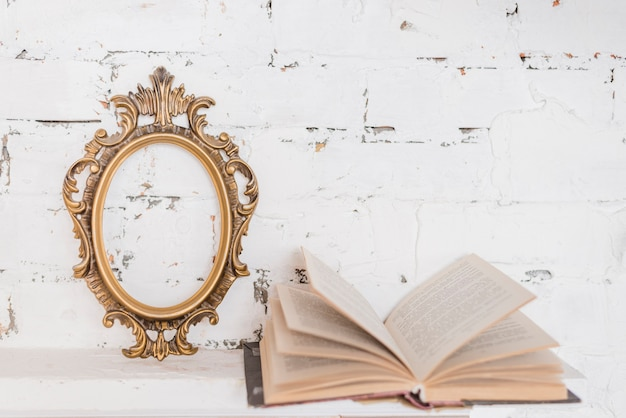 Overladen uitstekend frame en een open boek tegen witte muur