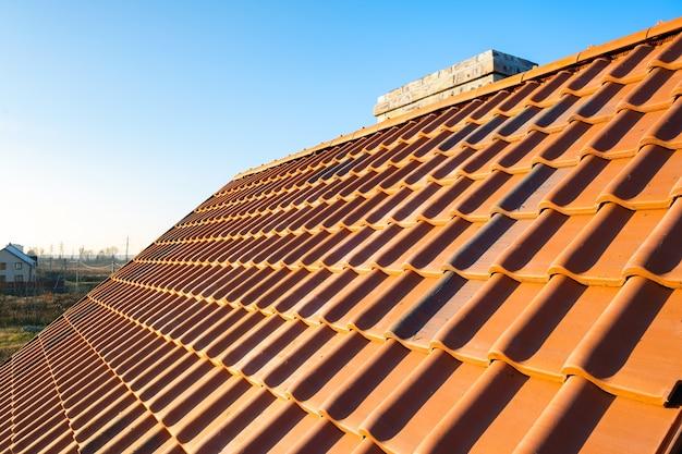 Overlappende rijen gele keramische dakpannen die het dak van de woningbouw bedekken.