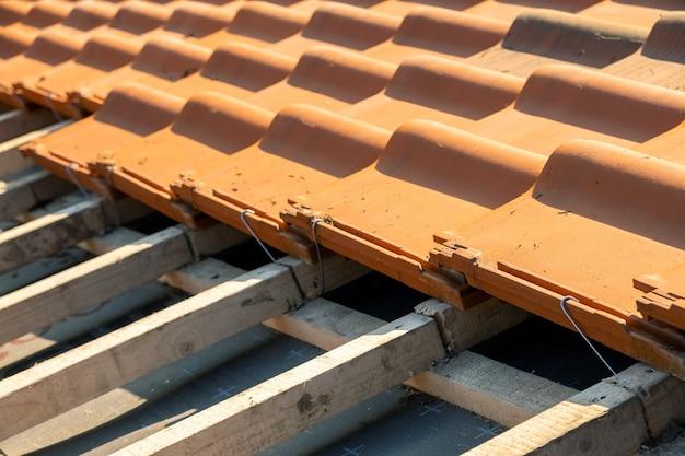 Overlappende rijen gele keramische dakpannen gemonteerd op houten planken die het dak van de woningbouw in aanbouw bedekken.