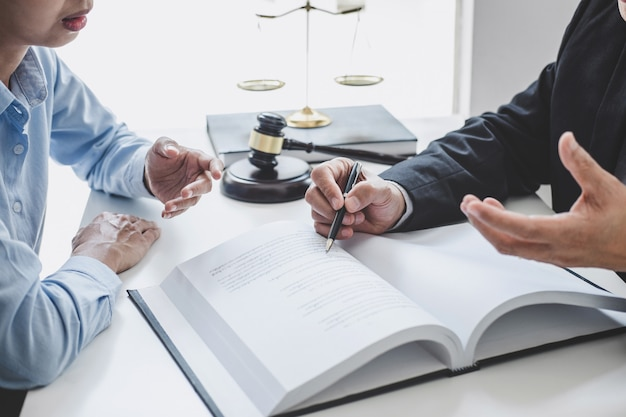 Overleg en conferentie van mannelijke advocaten en professionele zakenvrouw werken en discussie met advocatenkantoor op kantoor. concepten van recht, rechterhamer met schalen van rechtvaardigheid
