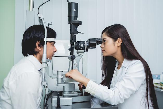 Overleg met een oogarts. jonge aziatische man en vrouwenarts