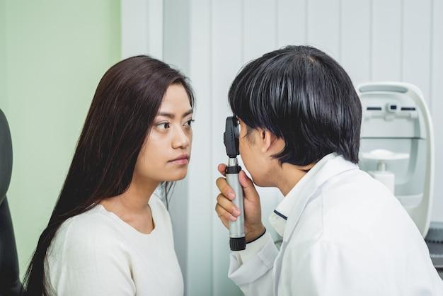 Overleg met een oogarts. jonge aziatische vrouw en arts