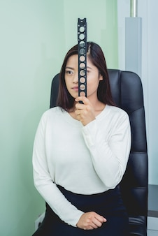 Overleg met een oogarts. jonge aziatische vrouw in kliniekbureau.