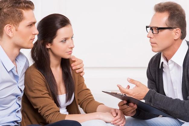 Overleg met gezinspsychiater. mooie jonge paar luisteren naar de psychiater die iets vertelt en gebaren?