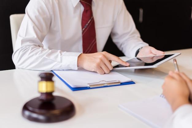 Overleg tussen een mannelijke advocaat en een klant over wet- en regelgeving