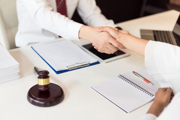 Overleg tussen een mannelijke advocaat en een zakelijke klant over wet- en regelgeving.