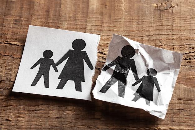 Overlijden ouder met kind. stuk papier met ouders en kinderen is doormidden gescheurd.
