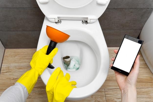Overlopend kapot toilet. verstopt toilet. een smartphone met een wit scherm voor reclame over sanitair. vrouw op zoek naar hulp voor een uur aan de telefoon. mockup.