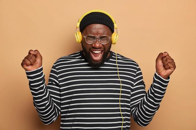 Overmatige zwarte man danst met opgeheven vuisten, draagt een koptelefoon op de oren