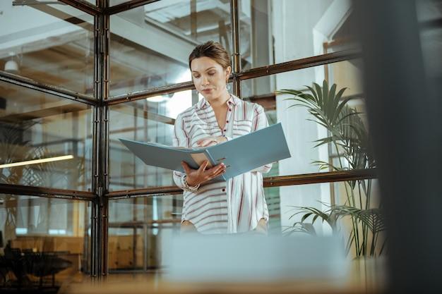 Oversized blouse. zwangere professionele interieurontwerper met een oversized blouse die hard aan het werk is
