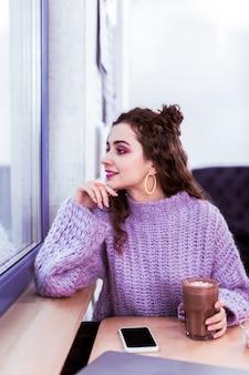 Oversized paarse trui. donkerharige schattig meisje tijd doorbrengen in een gezellig café en kijken op het straatleven