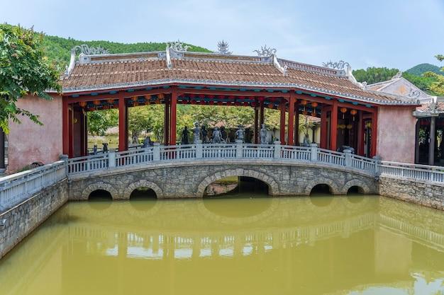 Overspannen brug door een decoratieve vijver op een japanse tropische tuin in danang, vietnam. reis- en architectuurconcept