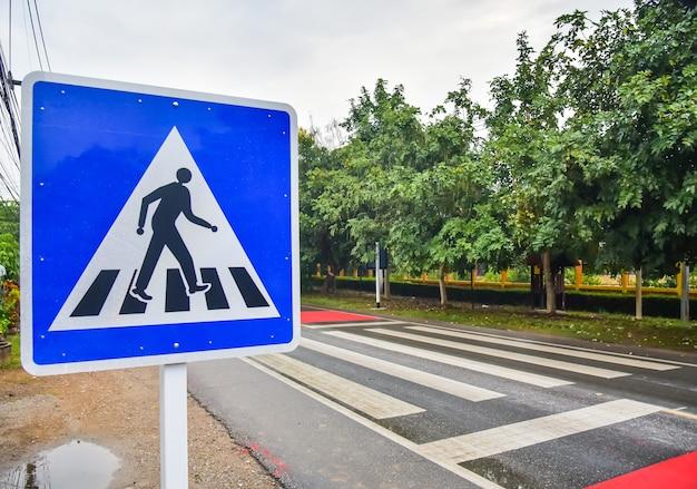 Oversteekplaatsbord op de weg voor veiligheid wanneer mensen op straat lopen
