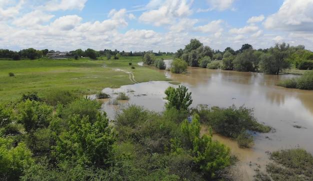Overstroomd veld met boerderij na zware regenbui