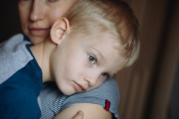 Overstuur jongen lag op de schouder van zijn moeder mon knuffelde zoon