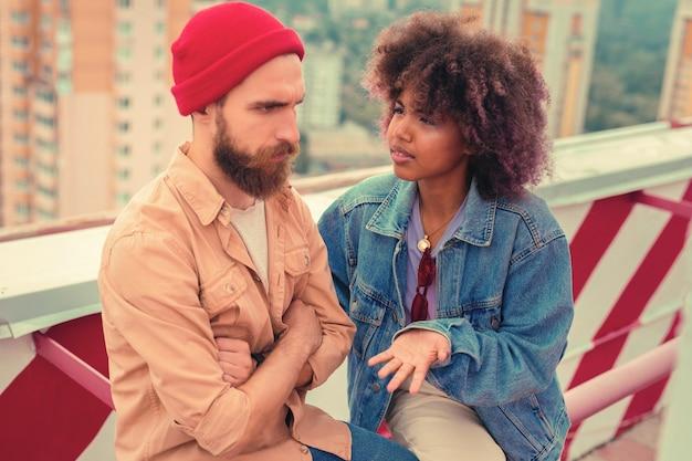 Overtreding. strikte jonge man zit met zijn armen gekruist en voelt zich beledigd terwijl zijn emotionele jonge vriendin met hem probeert te praten