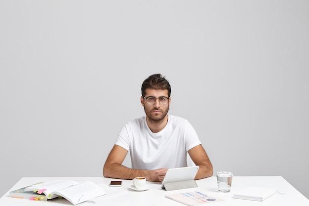 Overtuigde blanke man met stoppels en trendy kapsel, draagt een casual t-shirt
