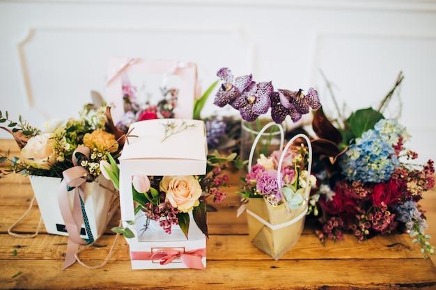 Overvloed aan bloemen. dozen met bloemen staan op een houten tafel. bloemenwinkel. balie in de bloemenwinkel.