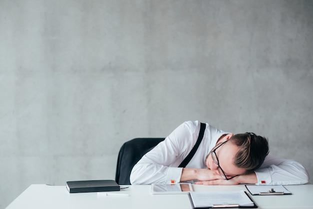 Overvolle agenda. kantoorroutine. portret van vermoeide jonge kerel slapen op de werkplek. ruimte kopiëren.