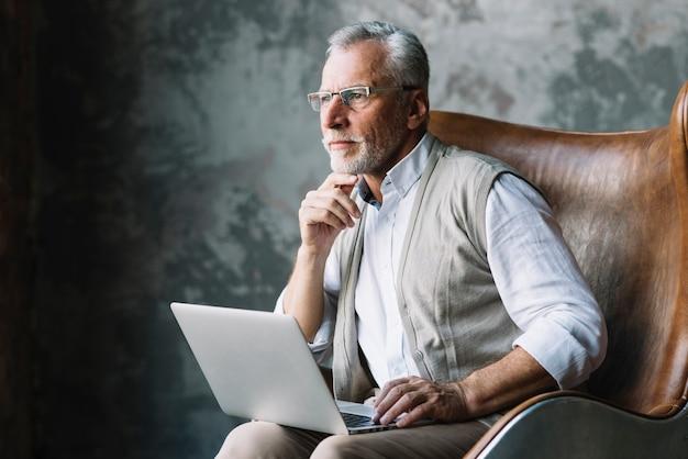 Overweegt bejaarde die op stoel met laptop tegen grungeachtergrond zit