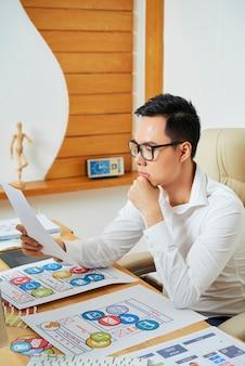 Overweegt een jonge ux-ontwerper die naar een document kijkt met de lay-out van de mobiele applicatie die hij heeft gemaakt