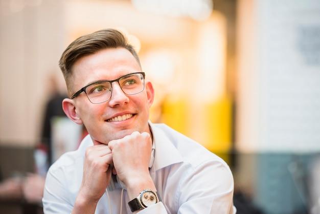 Overweegt glimlachende jonge mens die oogglazen met kin op zijn hoofd draagt