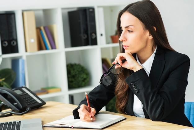 Overweegt jonge zakenvrouw met potlood over dagboek op het bureau