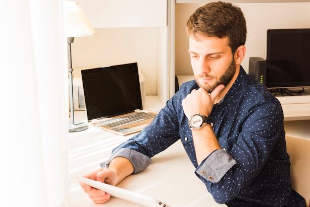 Overweegt knappe jonge mens die digitale tablet bekijkt