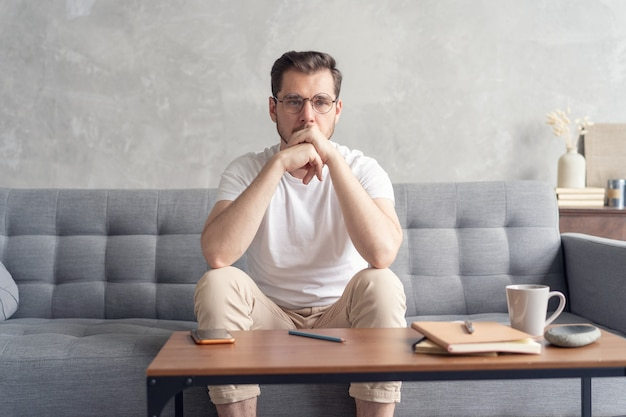 Overweegt serieuze man zittend op de bank alleen thuis