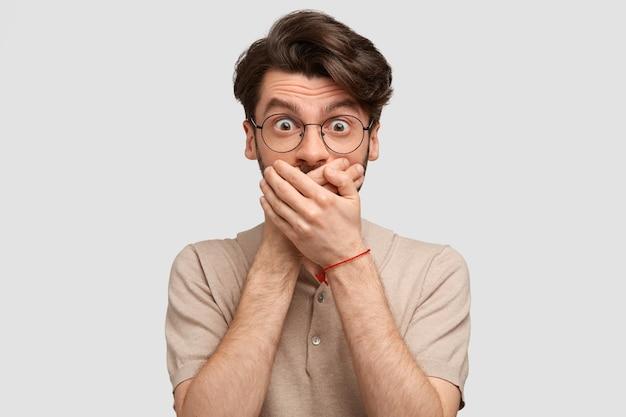 Overweldigd bang man met trendy kapsel sluit mond met handen, probeert stom te zijn, vraagt zich iets ongelooflijks af, gekleed in een casual beige t-shirt