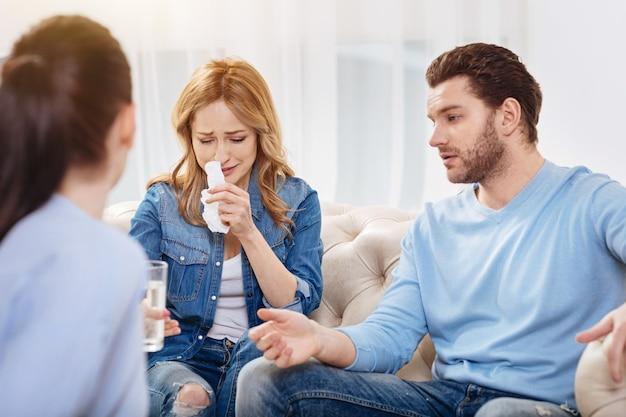 Overweldigd door emoties. ongelukkige trieste jonge vrouw die haar neus afveegt met een tissue en een glas water neemt terwijl ze de psycholoog vertelt over haar familieproblemen