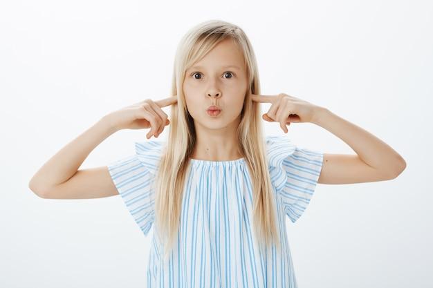 Overweldigd opgewonden schattig meisje met blond haar, pruilend met gevouwen lippen en oren bedekkend met wijsvingers, ongericht en verveeld, ongehoorzaam zijn tijdens het winkelen met moeder
