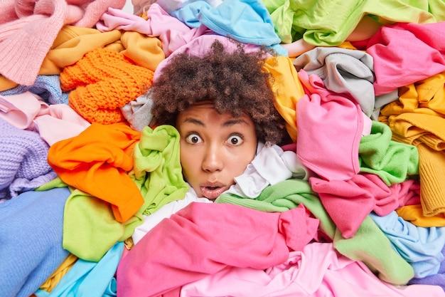 Overweldigde afro-amerikaanse vrouw geeft advies om je oude kleren te recyclen, steekt uit je hoofd door veelkleurige kleding omringd door ondraagbare spullen die zijn ingezameld voor donatie. textielrecycling