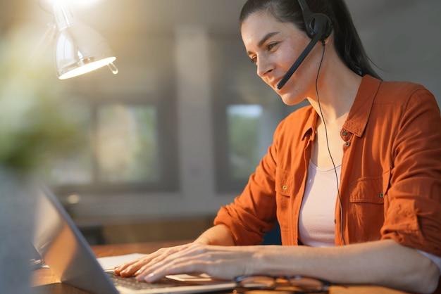 Overweldigend brunette die op computer thuis werken