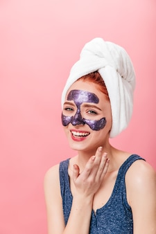 Overweldigend kaukasisch meisje dat huidverzorgingsbehandeling doet. studio shot van lachende vrouw met gezichtsmasker poseren op roze achtergrond.